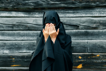 A beautiful, young, Muslim girl in a black veil with a closed face on the background of a gray tree prays. Copy space.
