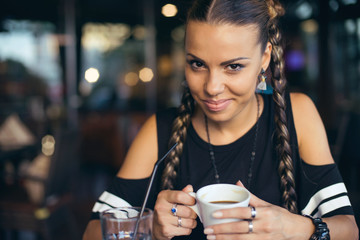Woman with pigtails drinking coffee in trendy cafe.