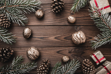 Brown wood background. Fir branches, cones and decorative walnuts. Gifts for xmas. Christmas greeting card and new year. Xmas and Happy New Year composition. Flat lay, top view