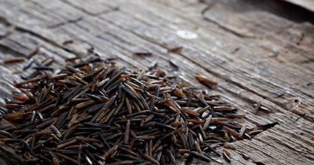 Heap of raw wild rice on an old wooden table Fotomurales