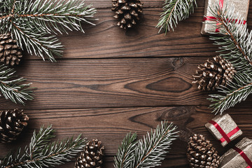 Brown wood background. Fir branches, decorative cones. Space for the message. Gifts for xmas. Christmas greeting card and new year. Xmas and Happy New Year composition. Flat lay, top view
