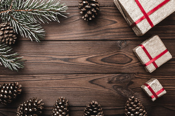 Brown wood background. Fir tree, decorative cones. Message space for Christmas and New Year. Gifts for xmas. Greeting card. Xmas and Happy New Year composition. Flat lay, top view