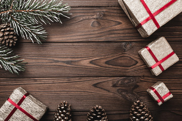 Brown wood background. greeting card. Fir tree, decorative cones. Message space for Christmas and New Year. Gifts for xmas. Xmas and Happy New Year composition. Flat lay, top view
