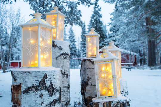 Close Up Of Group Of Burning Lanterns On The Tree Stumps In The Snow  Christmas Season Holiday and Decors. Selective Focus