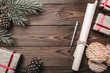 Brown wood background. Fir tree, decorative cone. Message space for Christmas and New Year. Sweets and gifts for holidays. Letter for Santa. Xmas and Happy New Year composition. Flat lay, top view