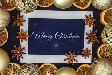 Christmas card with golden bubbles, dried orange, anise and white frame with stars on the blue background from the top