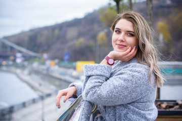 A woman of plus size, American or European appearance walks in the city enjoying life. A young lady with excess weight, stylishly dressed in coat at the center of the city. Natural beauty