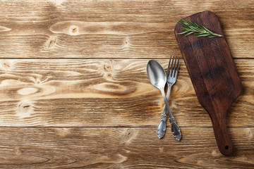 Cooking background concept. Vintage cutting board and cutlery. Top view with copy space.