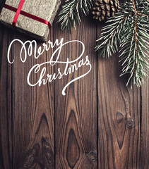 Brown wood background. Fir tree, decorative cone. Message space for Christmas and New Year. Gift for holidays. Xmas and Happy New Year composition. Flat lay, top view