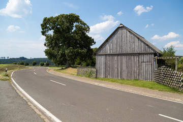 Old wooden barn along a rural road in Germany
