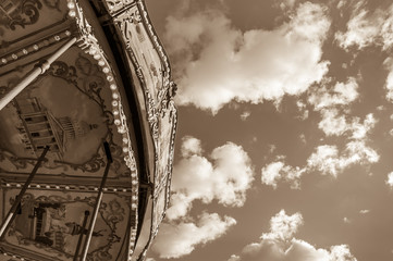 Old Parisian carousel against sky with clouds in sunny day. Sepia.