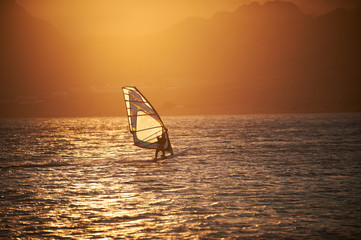 Sportman windsurfer on the sea surface against mountains at sunset time