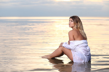 fashion photography with pretty woman in the water at sunset