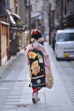 traditional japanese costumes kimono worn by a maiko with all the make up and tattos walking in the streets of gion corner kyoto japan