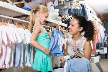 Woman with small girl choosing blue clothes