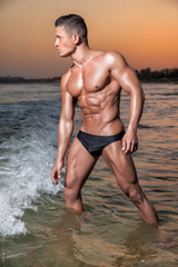 Muscular young sexy wet guy in a speedo posing in the sea at sunset