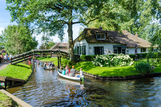 """Giethoorn, Netherlands: View of famous Giethoorn village with canals and rustic thatched roof houses.The beautiful houses and gardening city is know as """"Venice of the North"""""""