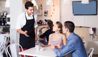 Smiling couple guests giving order to welcoming waiter