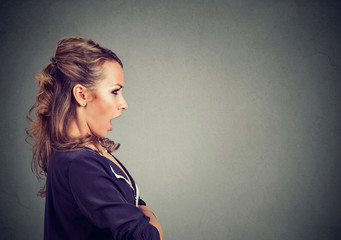 Side profile of a scared shocked woman isolated on gray background