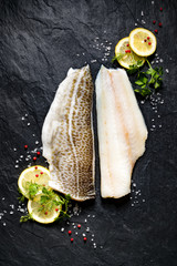 Fresh fish,  raw cod fillet with addition of herbs and lemon slices on black stone background, top view