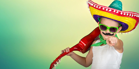 Mexican party.Boy with a fake mustache in a sombrero playing the guitar.