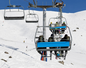 Skiers with backpacks on chair-lift