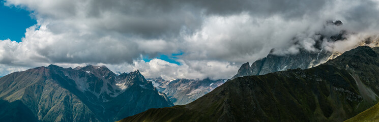 Amazing panoramic view to misty Caucasus Mountains.  Densely dark coniferous forests and high mountain peaks. Sunny day with blue mountains. Svaneti, Geogria.