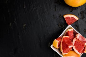 Sliced Grapefruits on a slate slab (selective focus)