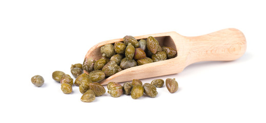 Capers in wooden spoon isolated on white background. Pickled capers. Canned capers