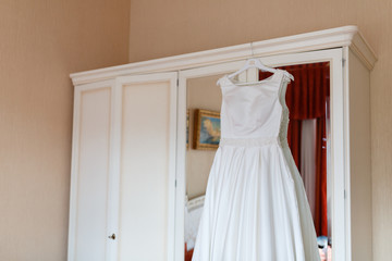 Wedding dress hanging on the wardrobe in the bedroom. The wedding collection. Classic expensive dress for a wedding or celebration in the room of an expensive hotel. Closeup