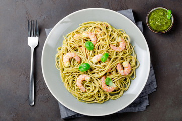 Spaghetti with fried prawns and pesto sauce in a gray plate, dar