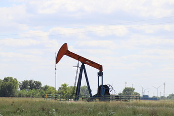 Pump jack in pasture with fence and equipment with wind turbines in the background