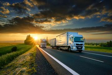 Fotobehang - Overtaking trucks on an asphalt road in a rural landscape at sunset