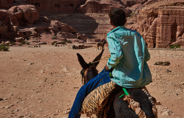 Bedouin child ride your donkey inside the ancient city of Petra , Jordan
