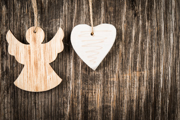 Christmas angel and heart over wooden background