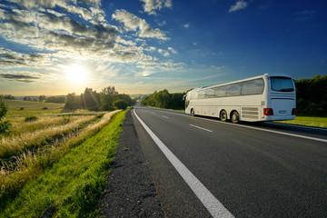 Fotobehang - White bus traveling on the asphalt road in a rural landscape at sunset