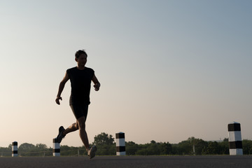Asia young man running in the time during sunrise on dam road exercise.Healthy lifestyle