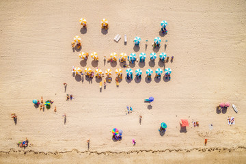 Top view of summer beach scene with colorful umbrellas and people sunbathing in Miami Beach, Florida, USA.