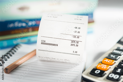 grocery shopping list on notebook with calculator and pencil money