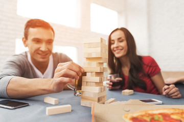 The company of young people plays a table game called jenga.