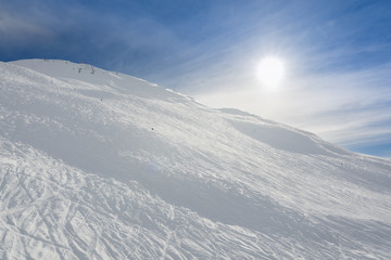 Advanced black steep ski trail, with sun behind the mountain