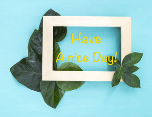 Have a nice day on wooden frame with fresh green leaf decorate on blue background