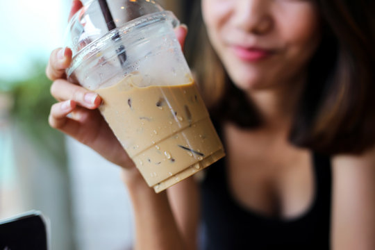 Portrait of smiling beautiful woman drinking cold coffee