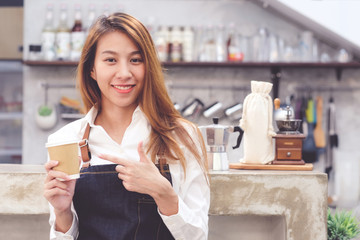 Young asia woman barista holding a diaposable coffee cup with smiling face at cafe counter background, small business owner, food and drink industry concept