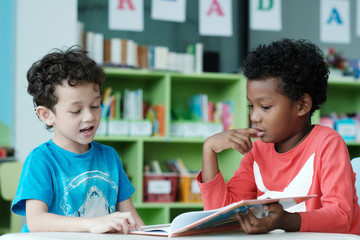 American and African boys are reading and studying together with happiness in their classroom, kid education concept