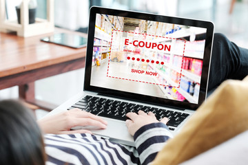 Woman entering the discount coupon code on laptop computer to get the grocery shopping on line promotion, on line shopping ,digital marketing business and technology, lifestyle concept