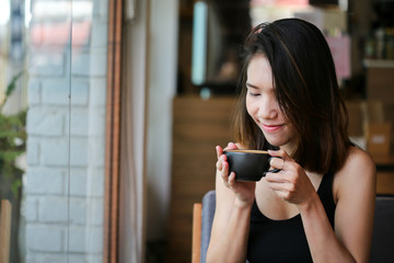 A beautiful woman and hot coffee of latte art cup before drinking in loft cafe