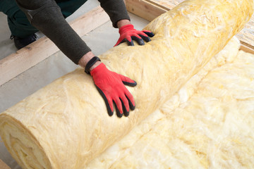 worker insulates the floor with mineral wool