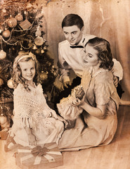 Christmas family photo with mother, father and girl. Black and white Xmas vintage image with child by home interior.