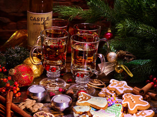 Christmas table with punch and hot wine. Xmas decorations and candles in composition. Pine branch and holiday cookies.